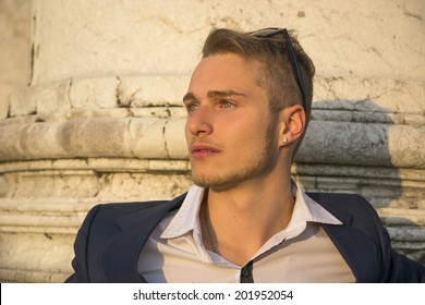 Handsome blond young man with marble columns behind him, looking away