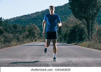 Handsome blonde athlete runner jumping at the middle of a highway.