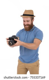 Handsome blonde beard man wearing blue T-shirt and beige pants with a beige hat, guy smiling and holding a camera, isolated on white background