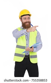Handsome blonde beard young engineer  holding a clipboard and pointing to something, guy wearing gray shirt and black pants with a yellow vest and yellow helmet, isolated on white background