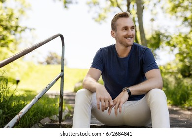 Handsome blonde man in a blue shirt and beige pants sitting down on steps outdoors on a sunny summer day with a big smile on his face.