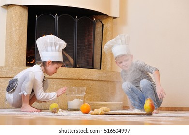 Handsome blue eyed kids in chef's hats near the fireplace: girl dressed in a toque playing cook with her cousin, theyâ??re totally stained with flour keep sprinkle each other with flour