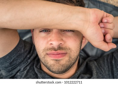 Handsome blue eyed young man looks at the camera, squinting and shielding eyes from the sun with his arm. Laying on the ground on a blanket outside.