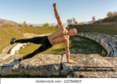 Handsome Body builder Man does phisical exercises outdoor. Innovative Gym in an ancient Roman amphitheater