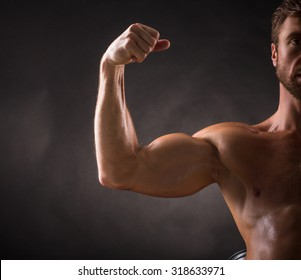 Handsome bodybuilder demonstrating his biceps in studio. Tanned shirtless man preparing for competitions.