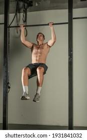 Handsome bodybuilder doing pull-ups on horizontal bar in a indoors modern gym.