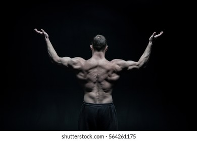 handsome bodybuilder man or sexy muscular guy with athlete body and back training and posing on black background