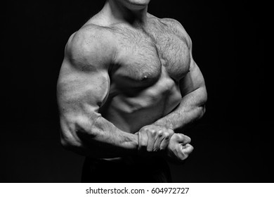 handsome bodybuilder man or sexy muscular guy with athlete body, torso and chest training sport and posing in gym, black and white
