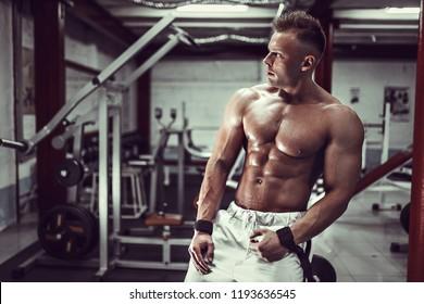 Handsome Bodybuilder resting after workout in gym