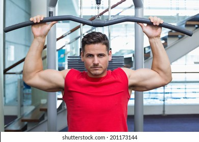 Handsome bodybuilder using weight machine for arms at the gym