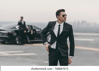 handsome bodyguard with security earpiece putting hand on gun