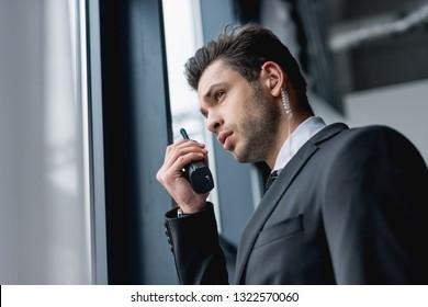 handsome bodyguard in suit using walkie-talkie