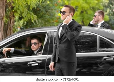 Handsome bodyguards near car outdoors