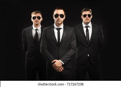 Handsome bodyguards on dark background