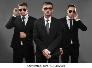 Handsome bodyguards on grey background