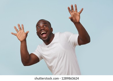 Handsome bold black man in white T-shirt is smiling, against pale blue background. Сrazy eyes, eyebrows raised. Wow gesture. Grimacing.
