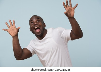 Handsome bold black man in white T-shirt is smiling, against pale blue background. Crazy eyes, eyebrows raised. Wow gesture. Grimacing.