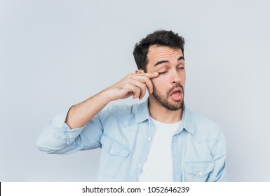 Handsome bored sleepy bearded male after long overwork on new project, wants to sleep in the morning, wearing blue shirt isolated on white studio background with copy space for advertising text.