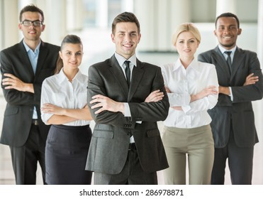 Handsome boss standing in a modern office with colleagues.