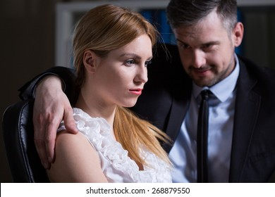 Handsome boss touching inappropriate his young pretty secretary