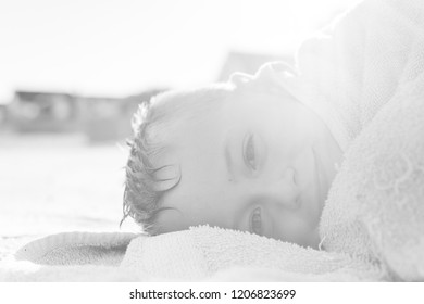 A handsome boy with ADHD, Autism, Asperger Syndrome lies down to go to sleep on a hot summers day wrapped in a towel