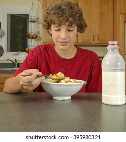 Handsome boy, age twelve, eating cereal for breakfast