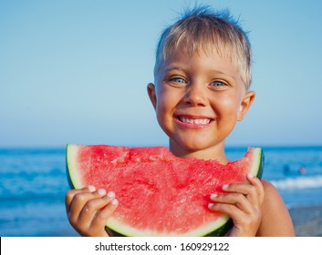 Handsome boy eating slice of watermelon on the beach