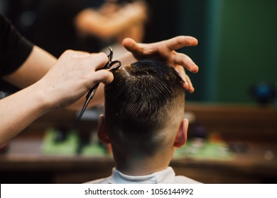 Handsome boy getting his hair and beard cut at barber shop, rear view