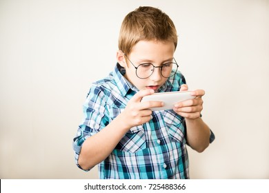 Handsome boy in glasses plays tablet. The concept of poor eyesight, harm of gadgets, myopia.
