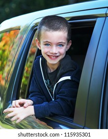 Handsome boy hanging out car window in the fall