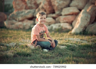 Handsome boy kid posing in summer central park on green fresh grass wearing stylish clothes and sun glasses shades.