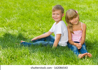 A handsome boy and a pretty girl are sitting on the green lawn in a summer day