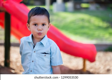 A handsome boy standing in front of a playgound slide with pouting lips and looking upset, moody or with a confrontational attitude.