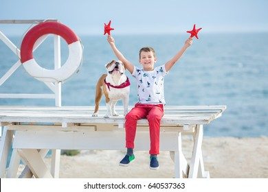 Handsome boy teen happy spending time together with his friend bulldog on sea side Kid dog holding playing two sea stars close to life buoy float wearing red pants trousers slippers and t-shirt
