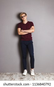 Handsome boy teenager stands with crossed arms near wall in grey studio