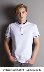 Handsome boy teenager stands with hands in pockets near wall in grey studio