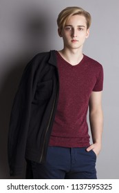 Handsome boy teenager in t-shirt with jacket stands near wall in grey studio
