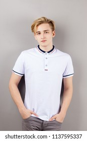 Handsome boy teenager in white shirt stands with hands in pockets near wall in grey studio