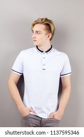 Handsome boy teenager in white shirt stands with hands in pockets and looks away near wall in grey studio