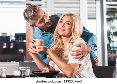 handsome boyfriend hugging smiling girlfriend during date in cafe