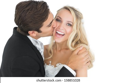 Handsome bridegroom kissing his wife on her cheek while embracing her