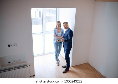 handsome broker holding clipboard and standing with beautiful woman in room