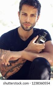 handsome brown man holding a fragrance