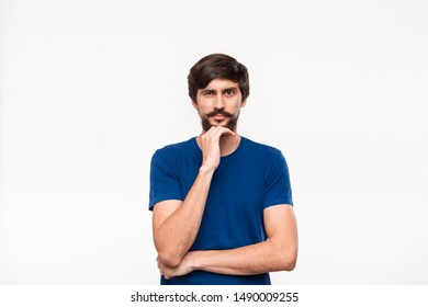 Handsome brunet man in a blue shirt holding arms folded over his chest and keeping hand close to face with sceptical emotion standing isolated over white background. Concept of doubt.