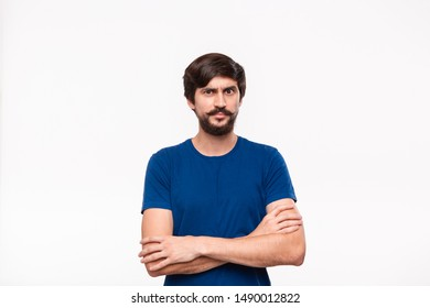 Handsome brunet man in a blue shirt holding arms folded over his chest with sceptical emotion standing isolated over white background. Concept of doubt.