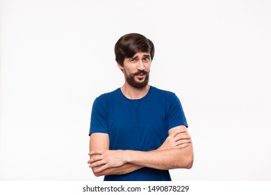 Handsome brunet man in a blue shirt holding arms folded over his chest with sceptical emotion standing isolated over white background. Emotion of doubt.