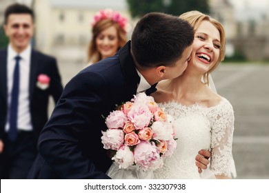 Handsome brunette groom kissing beautiful bride in wedding dress with bouquet bridesmaids in background