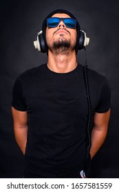 A handsome brunette guy with a beard of a hipster appearance in a black hat, glasses, a t-shirt poses on the camera on a dark background with studio headphones and looks up.