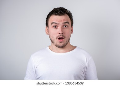 Handsome brunette guy with bristles in a white T-shirt makes funny grimaces on his face