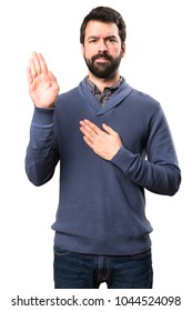 Handsome brunette man with beard making an oath on white background